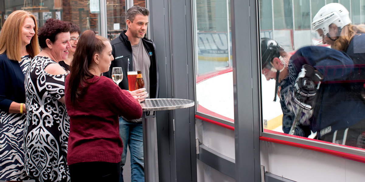 Guests watching an ice hockey game at a rinkside cocktail style function