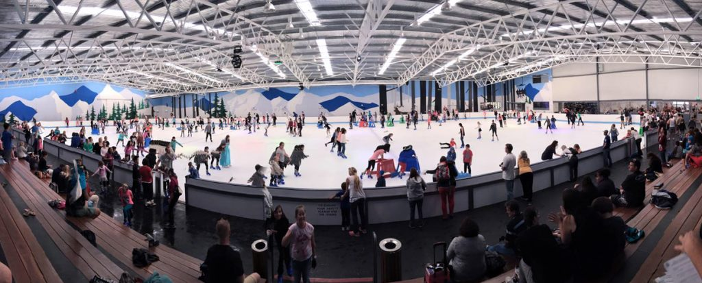 A large group of people ice skating during a fundraising event at Cockburn Ice Arena.