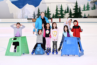 Birthday group having a photo taken with our party host on the ice.