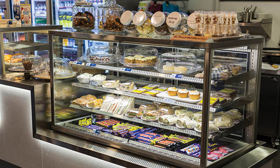Cold food cabinet in the frostbite cafe full of wraps, sandwiches, cakes and chocolates