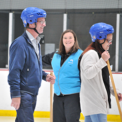 coach giving broomball instructions on ice