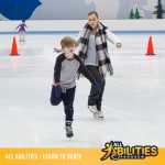 An ice skating coach is instructing a child on how to do a one foot glide