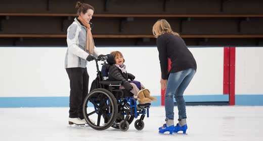 Girl in wheelchair being pushed on the ice during an All Abilities session