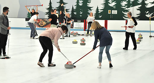 A Corporate team building function, trying curling on the ice.