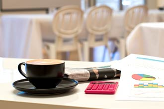 A cup of coffee, newspaper and calculator on a desk
