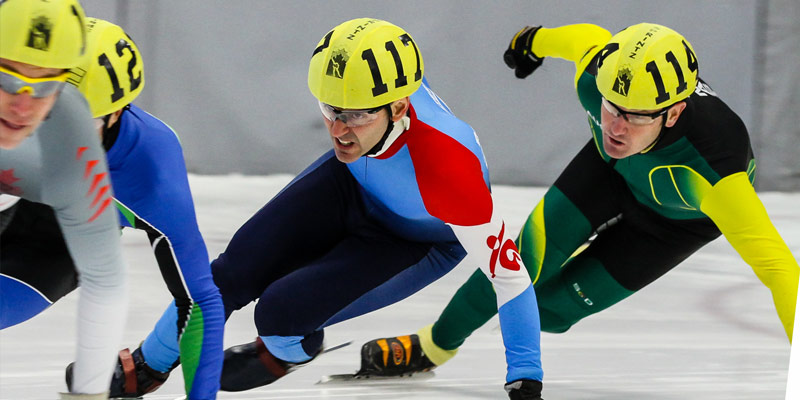 Three male ice speed skaters turning a corner.