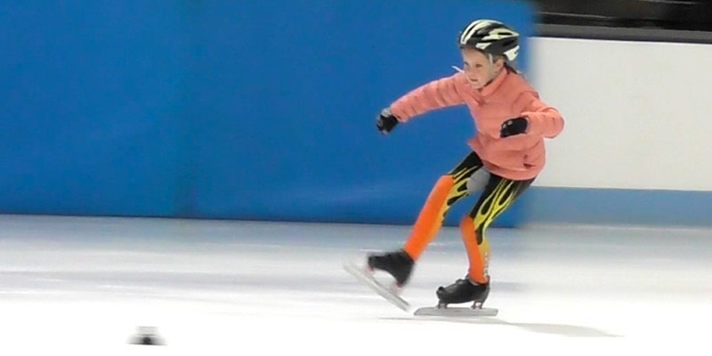 Young girl speed skater doing crossovers on the ice.